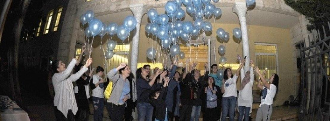 Children, therapists and parents releasing balloons into the sky